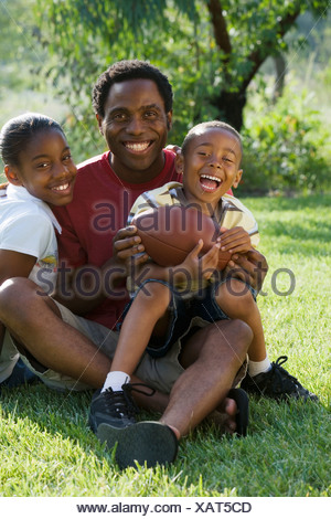Father sitting with two children 6 13 in park holding american football smiling portrait - Stock Photo