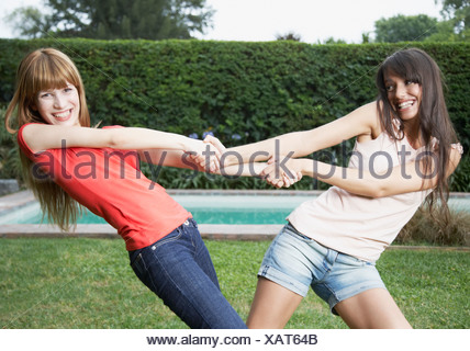 Two women outdoors pulling each others arms and smiling - Stock Photo