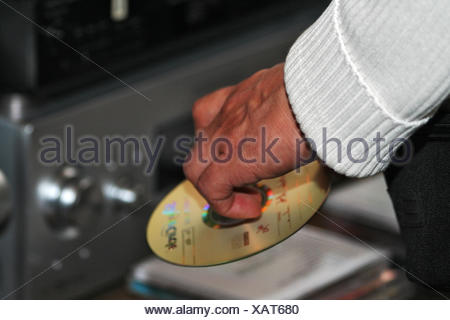hand finger music listen disc party celebration sweater hold serve grasp CD - Stock Photo