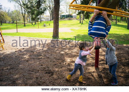 Father and two sons playing in a playground - Stock Photo
