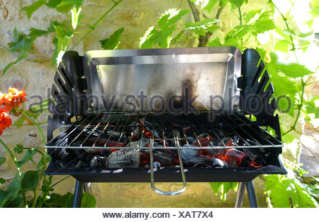 An empty BBQ showing the red hot coals heating up ready to start cooking - Stock Photo