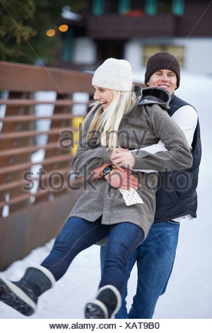 A young couple dressed warmly enjoy each others company in the mountains with a lodge in the background. - Stock Photo