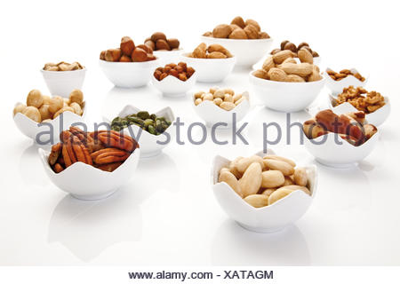 Assorted nuts and kernels in ceramic bowls, pecans, walnuts, hazelnuts, macadamia nuts, peanuts, almonds, pistachios - Stock Photo