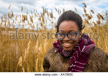 African American teenager girl dressed warm and laughing in front of a wheat field at the  Tryon Palace, New Bern, North Carolina, United States of - Stock Photo