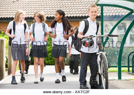 Students leaving school one with a bicycle - Stock Photo