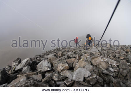 A group of climbers holding a rope on a rocky section while hikking up at the Nevado de Toluca volcano in Estado de Mexico, Mexico. - Stock Photo
