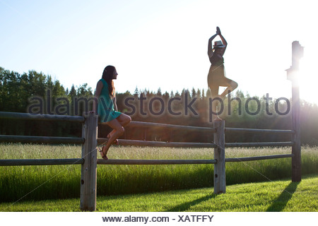 Two young women balancing on a wooden fence next to a green field. - Stock Photo