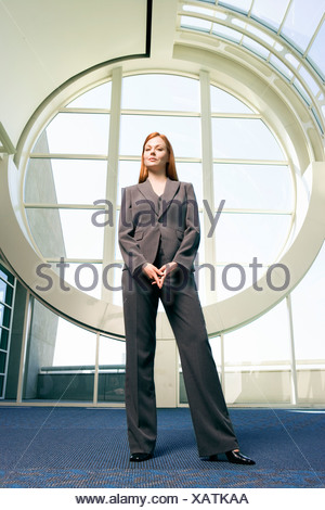 Confident businesswoman with ginger hair wearing grey suit smiling front view portrait surface level - Stock Photo