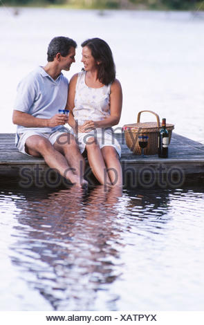 couple picnicking on a dock - Stock Photo