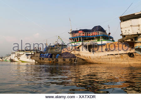 Pinisi, traditional two masted wooden cargo sailing ships moored in Sunda Kelapa Harbour, Jakarta, Java Island, Indonesia - Stock Photo
