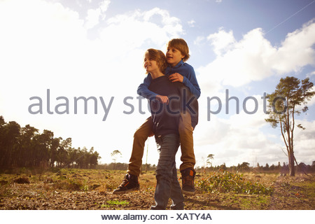Twin brothers playing piggy back in forest clearing - Stock Photo