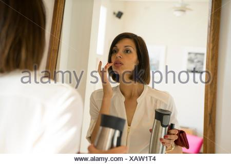 Mid adult woman applying lipstick in bedroom mirror - Stock Photo