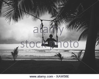 Silhouette of boy sitting on a swing on the beach - Stock Photo