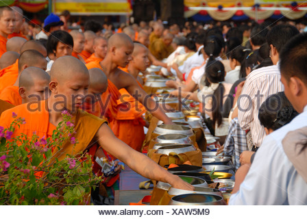 Theravada Buddhism, That Luang Festival, Tak Bat, monks standing behind alms bowls, believers, pilgrims giving alms - Stock Photo