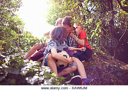 Boys playing in forest - Stock Photo