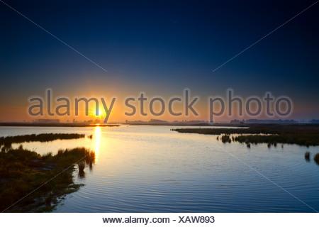 sun rising up over blue lake - Stock Photo