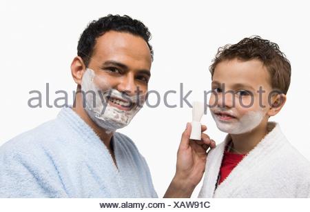 Man applying shaving cream on his son's face - Stock Photo