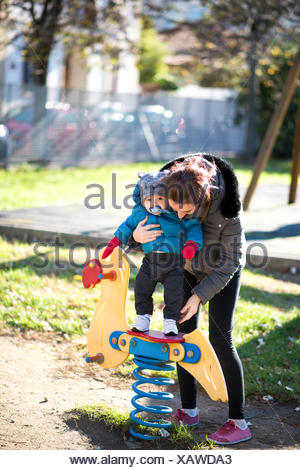Mother and son playing in a playground - Stock Photo