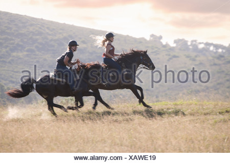Couple riding horses in rural landscape - Stock Photo