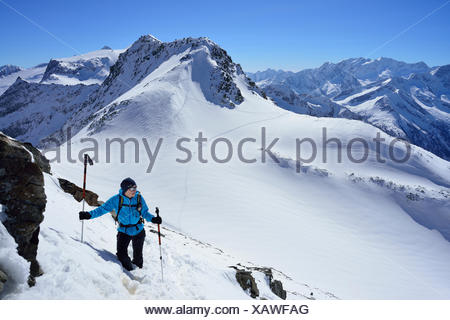 Female back-country skier ascending to Zwerchwand, Realspitze and Olperer in background, Zillertal, Zillertal Alps, Tyrol, Austria - Stock Photo