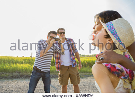 Man photographing female friends blowing bubble gum outdoors - Stock Photo