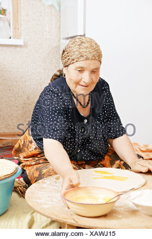 Senior woman taking bowl - Stock Photo