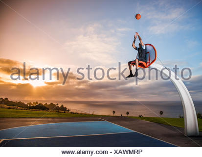 Young man sitting in a basketball hoop in a park, Los Angeles, California, USA
