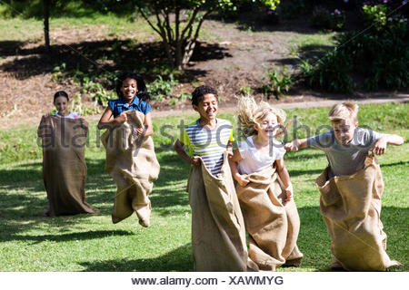 Children having a sack race in park - Stock Photo