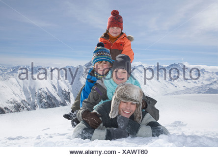 Portrait of young family in mountains on winter day - Stock Photo