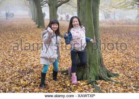 Two young girls playing in forest in autumn - Stock Photo
