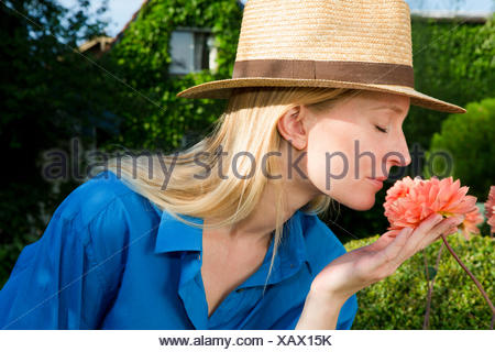 Close up of mid adult woman smelling garden bloom - Stock Photo
