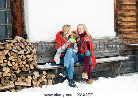 Two young female friends drinking coffee outside wooden cabin - Stock Photo