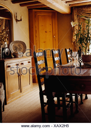 Antique oak table and ladderback chairs in cottage dining room with pine sideboard and tall freestanding corner cupboard - Stock Photo