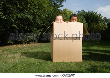 Boy and girl in a box - Stock Photo