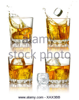 Set of scotch whiskey glasses with splash and ice isolated - Stock Photo