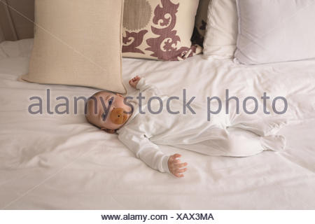 Cute little baby with pacifier in mouth sleeping on bed