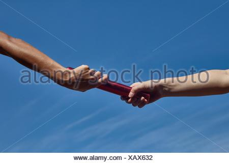 Hands of female relay runners passing baton against blue sky - Stock Photo