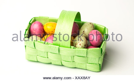 Speckled colourful easter eggs in a green basket - Stock Photo
