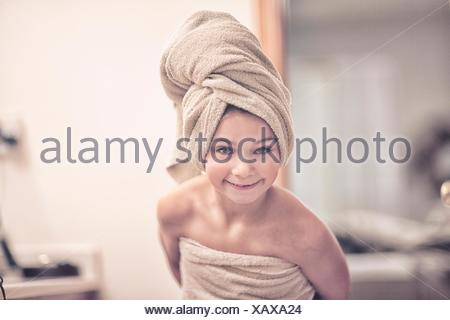 Girl wrapped in towel wearing towel on head looking at camera smiling - Stock Photo