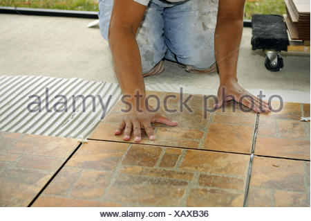 Male Hispanic Lays Ceramic Tile On Cement Floor In Patio Lanai Stock