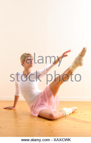 Beautiful ballet dancer lifting arm towards leg exercise woman ballerina - Stock Photo