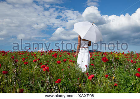 Woman with white umbrella standing in field of red poppies - Stock Photo