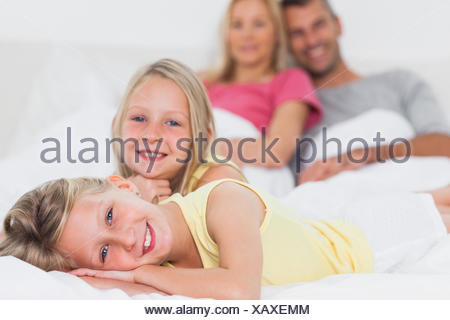 Cheerful twins posing in bed in front of their parents smiling on the background - Stock Photo