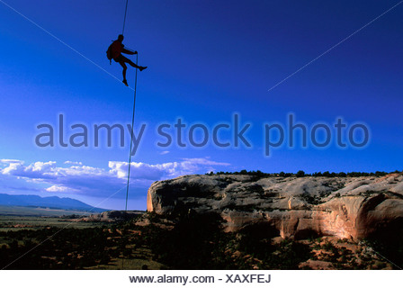 Man abseiling on rope in landscape of in Fisher Towers, Colorado River Waterway Near Castle Valley, Moab, Utah, USA - Stock Photo
