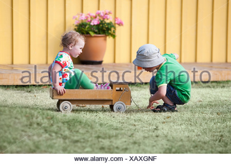 Two kids (2-5) playing in the garden - Stock Photo