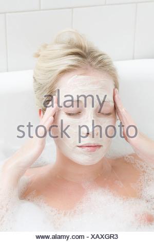 Woman wearing mask in bubble bath - Stock Photo