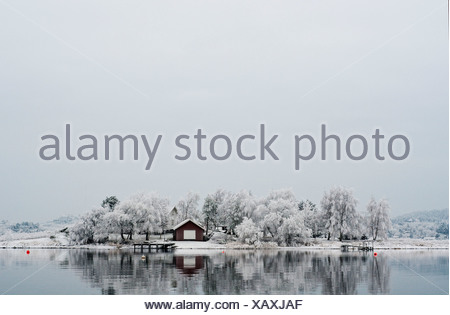 Beautiful view of country house and frosted trees reflected in peaceful lake against sky - Stock Photo