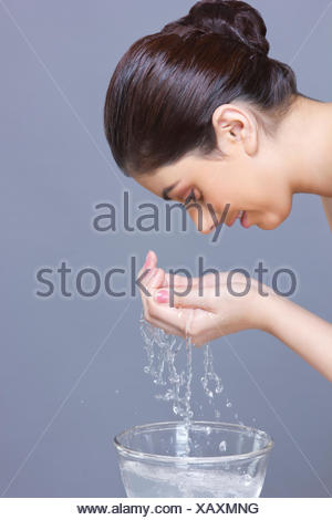Profile shot of young woman washing face with water over blue background - Stock Photo