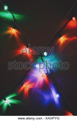 Close up of illuminated christmas lights hanging on wall - Stock Photo