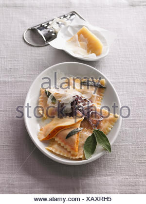Ravioli with red pesto and sage butter - Stock Photo